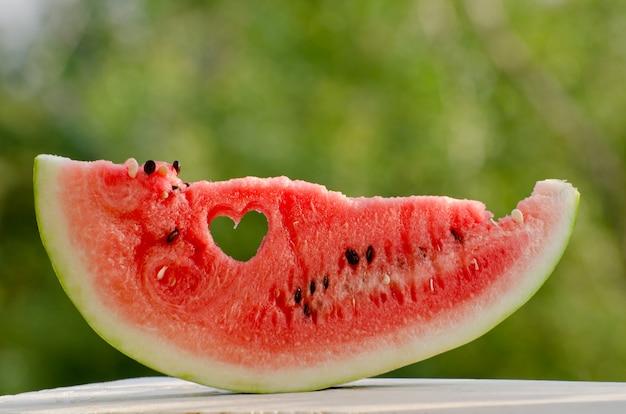 Große scheibe wassermelone mit einem herz, das vor dem hintergrund des grüns in das fleisch geschnitzt ist