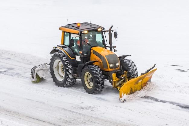 Große schneepflug-traktormaschine bei der arbeit auf der straße während eines schneesturms im winter.