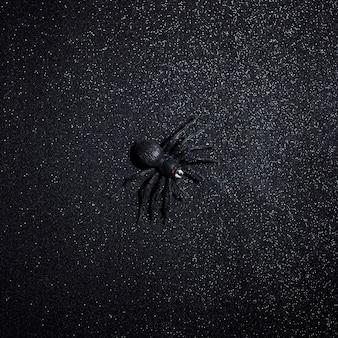 Große schwarze halloween-spinne über dunklem glitzerhintergrund