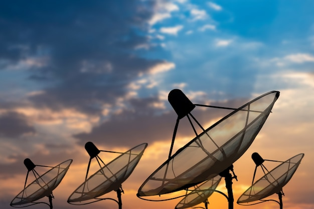 Große schwarze satellitenschüssel auf schönem spiralförmigen sonnenuntergangshimmelhintergrund, übertragungsdaten. digitaler technologiehimmelhintergrund.