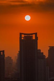 Große sonne, die über bangkok-stadtskyline, stadtbildsonnenuntergang steigt