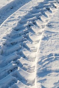 Große spuren des profils eines traktors oder eines anderen schweren landwirtschaftlichen fahrzeugs auf schneeverwehungen auf dem feld, nahaufnahme