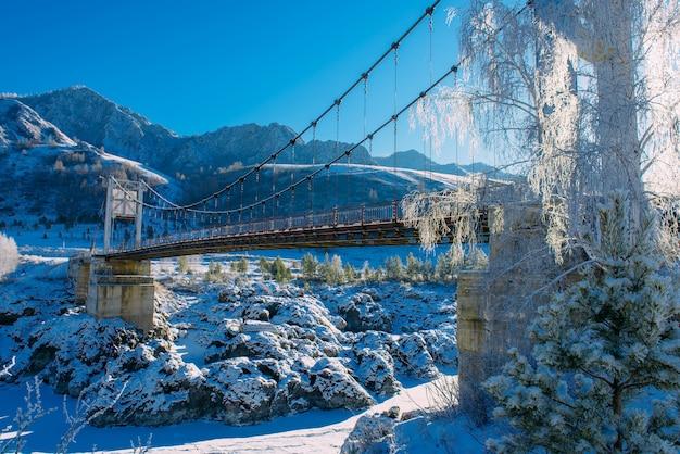 Große straßenbrücke über gefrorenem fluss vor dem hintergrund der schneebedeckten berghänge und des strahlend blauen himmels an einem sonnigen wintertag. atemberaubende frostige landschaft im altai-gebirge.