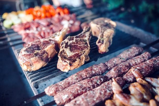 Große stücke in essig eingelegtes fleisch auf einem gitter in einem restaurant, gemischtes gegrilltes fleisch.
