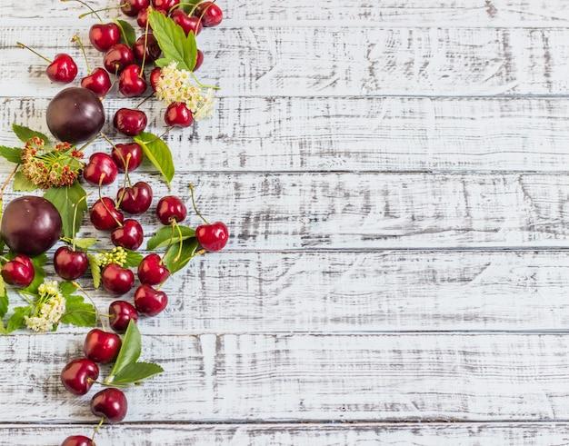 Große süße saftige kirschen, pflaumen und trauben, laub und blumen auf einem hölzernen hintergrund