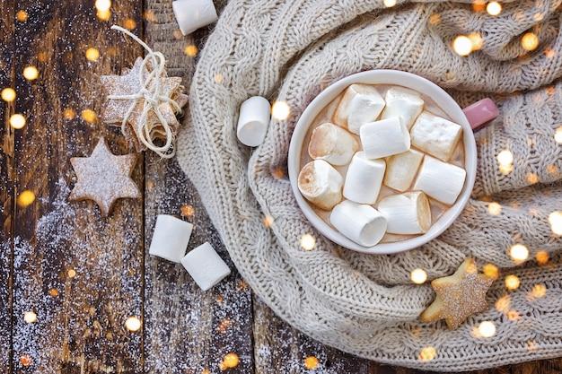 Große tasse cappuccino mit marshmallow und weihnachtsplätzchen auf braunem holztisch mit weihnachtslichtern.