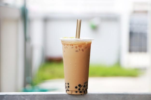 Große tasse eismilchtee mit bubble boba frisches und süßes getränk im taiwan-stil auf die stahlstange legen und hintergrund verwischen, essen und trinken konzept