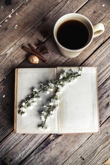 Große tasse kaffee auf vintage holztisch. frühlingsblumen und bücher. notizen in einem notizbuch