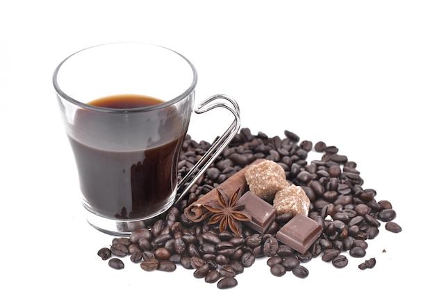 Große tasse kaffee in kaffeebohnen, anisstern, schokolade und zucker