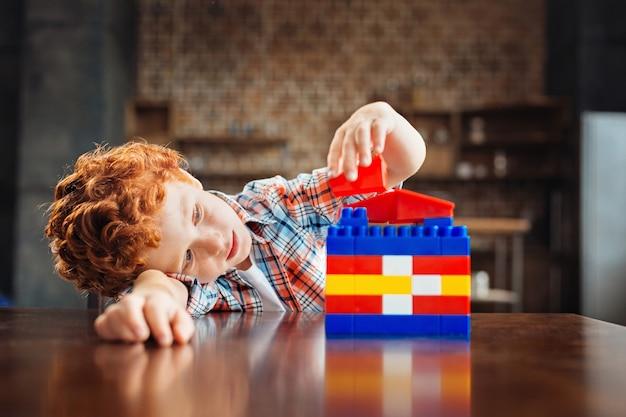 Große träume haben. nachdenklicher junge mit lockigen haaren, der auf einem tisch liegt und sich auf ein stück eines baukastens konzentriert, während er ein dach seines traumhauses baut.