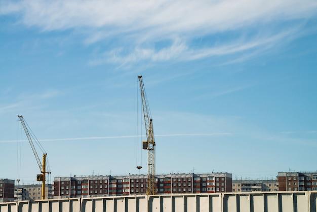 Große turmdrehkräne über im bau befindlichen gebäuden gegen blauen himmel. bild der konstruktionsnahaufnahme mit kopienraum. bau der stadt.