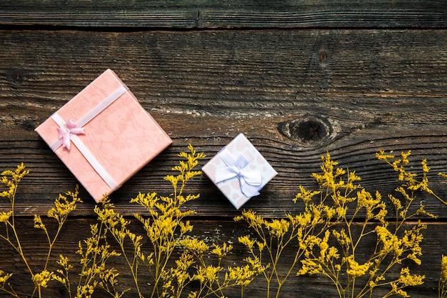 Große und kleine geschenke auf hölzernem hintergrund