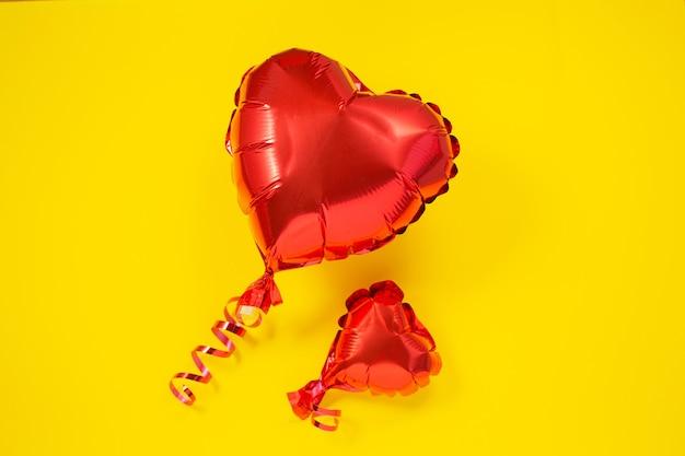 Große und kleine rote herzförmige folienballons. valentinstag