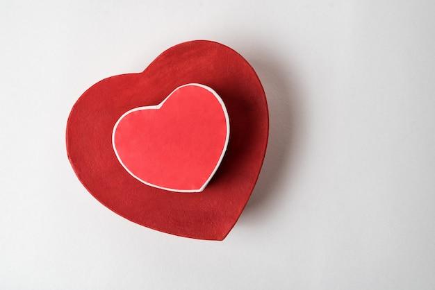 Große und kleine rote herzförmige kisten auf dem tisch. draufsicht. geschenke am valentinstag