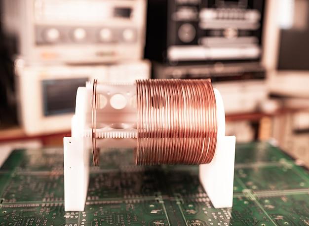 Große und kleine spulen in nahaufnahme mit kupferdraht stehen auf einem grünen mikroschaltkreis in einer fabrik für klassifizierte militärausrüstung. supergeheimes hochfrequenzkomponenten- und gerätekonzept Premium Fotos