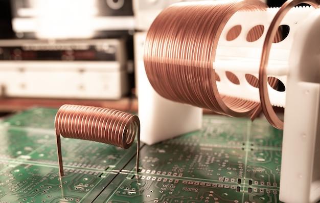 Große und kleine spulen in nahaufnahme mit kupferdraht stehen auf einem grünen mikroschaltkreis in einer fabrik für klassifizierte militärausrüstung. supergeheimes hochfrequenzkomponenten- und gerätekonzept
