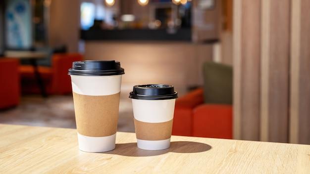 Große und kleine tasse kaffee auf einem holztisch in einem café. recycling-idee