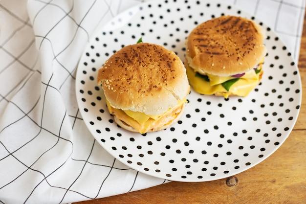 Große und leckere hamburger liegen auf einem teller mit schwarzen erbsen. holztisch und weiße karierte serviette.