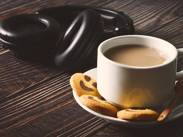 Große weiße tasse mit kaffee, schwarzem kopfhörer und gelben keksen mit fröhlichem lächeln auf dem holztisch. nahaufnahme. glücklicher morgen und arbeitspausenkonzept.