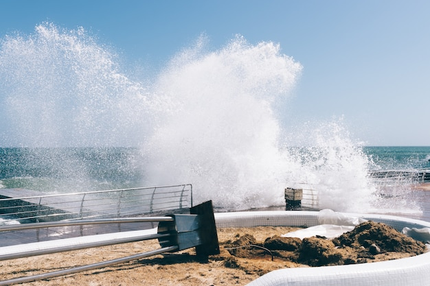 Große wellen brechen am damm und verursachen schäden