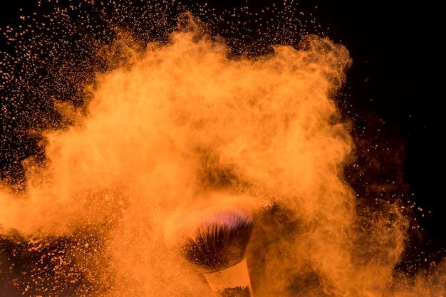 Große wolke des orange pulvers um make-upbürste auf dunklem hintergrund