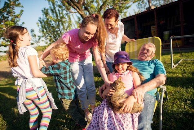 Großeltern haben spaß mit ihren enkelkindern im hinterhof an einem sonnigen tag.