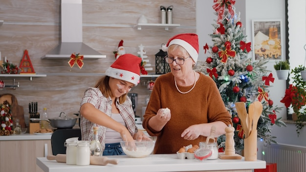 Großeltern helfen enkelkind, hausgemachten traditionellen keksteig in der kulinarischen küche zuzubereiten