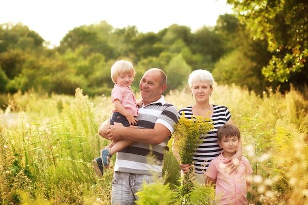 Großeltern mit enkelkindern im sommer auf dem feld