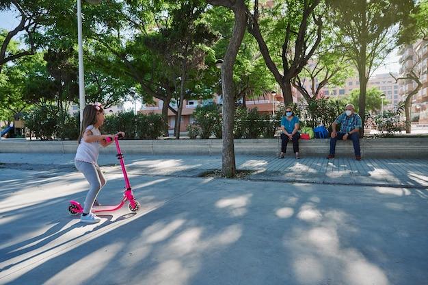 Großeltern mit maske gehen mit ihren enkelkindern in den park