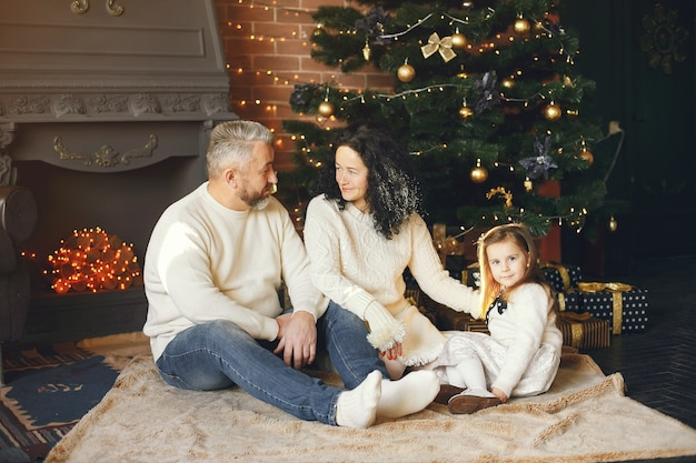 Großeltern sitzen mit ihrer enkelin. weihnachten feiern in einem gemütlichen haus.