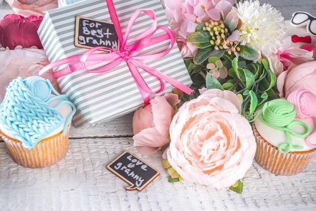 Großeltern-tagesfeiertagskonzept, großmutter- und großvater-tagesgrußhintergrund. süße hausgemachte cupcakes für oma und opa, mit der textinschrift ich liebe dich oma. mit geschenken und blumen