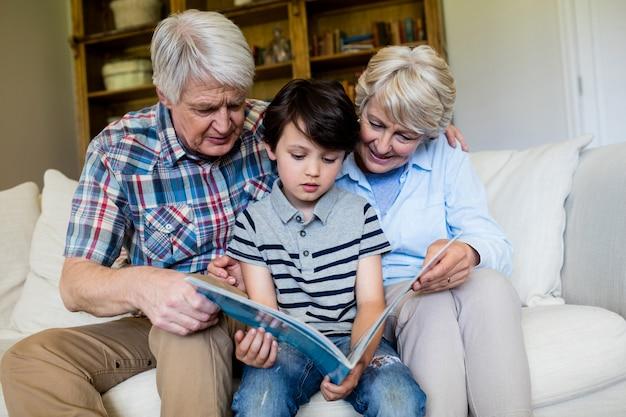 Großeltern und enkel, die buch im wohnzimmer betrachten
