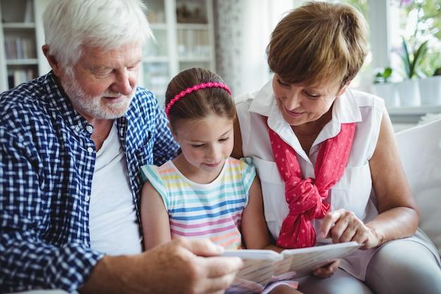 Großeltern und enkelin betrachten fotoalbum im wohnzimmer