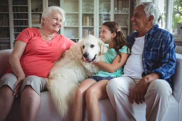 Großeltern und enkelin sitzen auf sofa mit hund