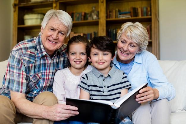 Großeltern und enkelkinder, die fotoalbum im wohnzimmer halten