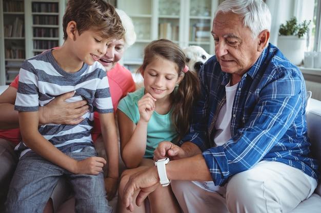 Großeltern und enkelkinder, die smartwatch im wohnzimmer betrachten