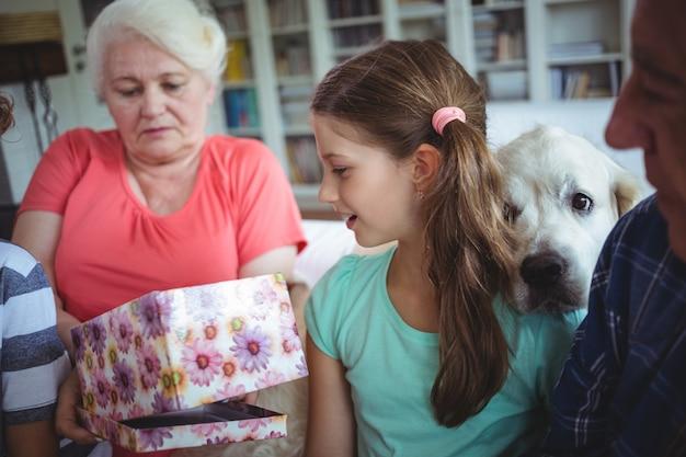 Großeltern und enkelkinder, die überraschungsgeschenk im wohnzimmer betrachten