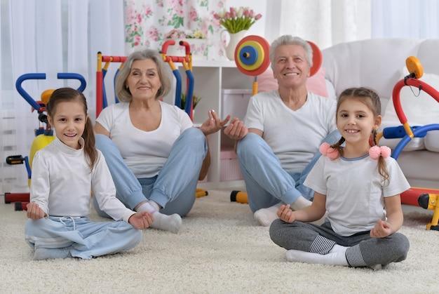 Großeltern und kleine enkelinnen machen heimübungen