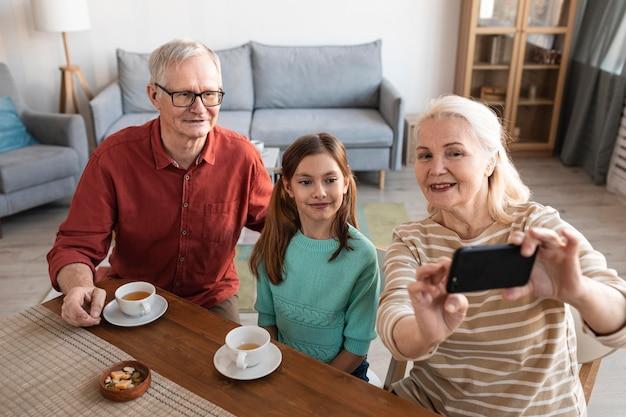Großeltern und mädchen machen selfie