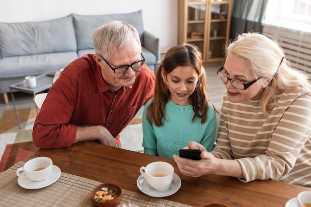 Großeltern und mädchen schauen auf telefon
