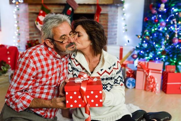 Großeltern zusammen mit geschenk-box in ihrem wohnzimmer
