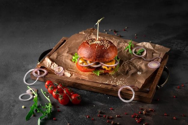 Großer amerikanischer vegetarischer burger auf schwarzem hintergrund. veganes schnitzel mit käse, tomaten und zwiebeln auf einem holztablett, kopierraum