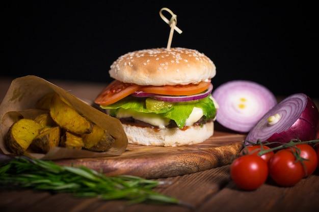 Großer appetitlicher burger mit rindfleisch, kartoffeln und käse auf einer holzoberfläche