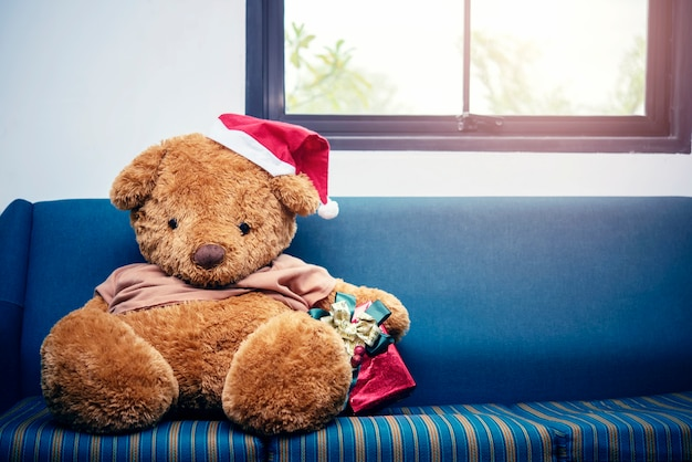 Großer bär mit weihnachtshut und roter geschenkbox auf sofa. frohe weihnachten hintergrund konzept.