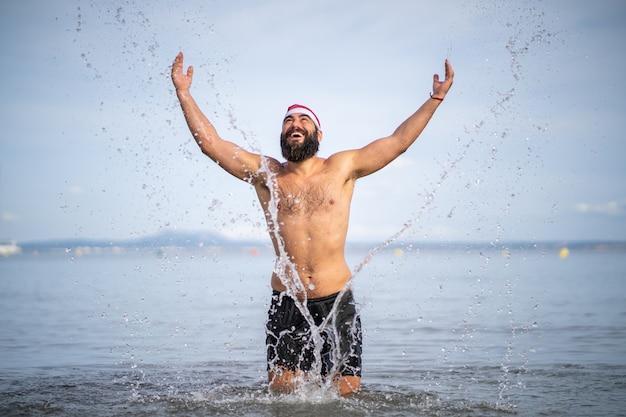 Großer bärtiger mann, der mit weit geöffneten armen wasser in einen strand spritzt, während er eine weihnachtsmannmütze trägt