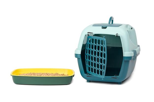 Großer blauer kunststoffträgerkäfig für katzen und hunde und katzentoilette gefüllt mit gepresstem sägemehl isoliert auf weiß