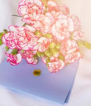 Großer blumenblumenstrauß mit umschlag auf tabelle
