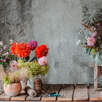 Großer blumengesteckblumenstrauß auf dem tischplattenfloristen auf dem hintergrund einer betonmauer