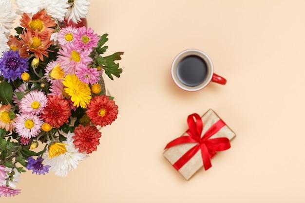 Großer blumenstrauß aus bunten verschiedenen blumen, tasse kaffee und geschenkbox auf beigefarbenem hintergrund. ansicht von oben. geringe schärfentiefe. konzentrieren sie sich auf blumen.