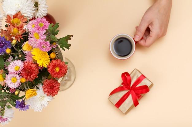 Großer blumenstrauß aus bunten verschiedenen blumen, weibliche hand mit tasse kaffee und geschenkbox auf beigem hintergrund. ansicht von oben. geringe schärfentiefe. konzentrieren sie sich auf blumen.